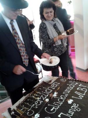 """Kulturbürgermeister Dr. Markus Raab schneidet den vom Verein der Freunde der WLB gespendeten Festtagskuchen an."""""""